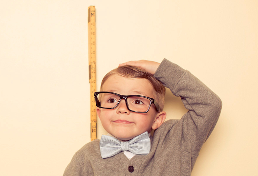 Young boy in black rimmed glasses measuring his own height with a tape measure.