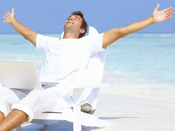 Man on tropical beach working happily on his computer with arms spread high over head