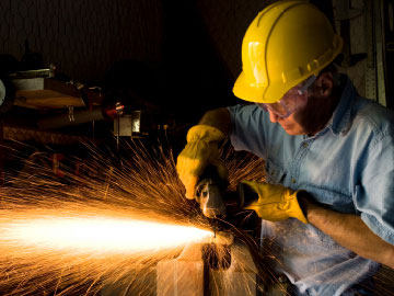 Manufacturing.  A man grinds metal causing sparks to fly everywhere.