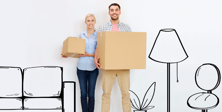 Young couple holding moving boxes for their new home