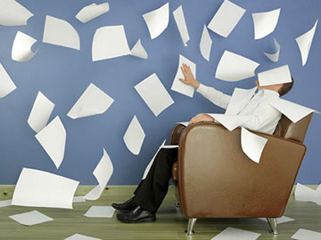 man in chair trying to organize papers flying everywhere!