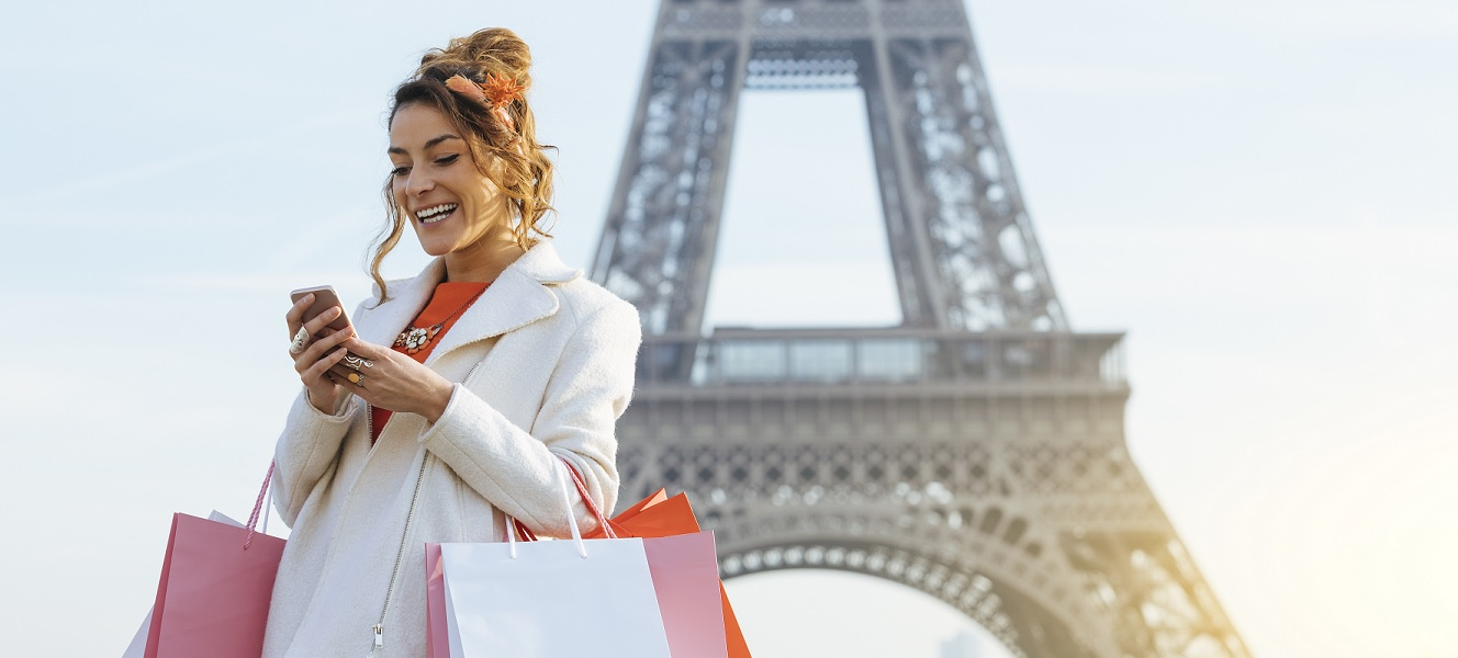 Eiffel Tower in background, woman with shopping bags is on her phone doing banking