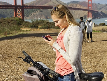 woman banking from her phone on bike in front of gold gate bridge
